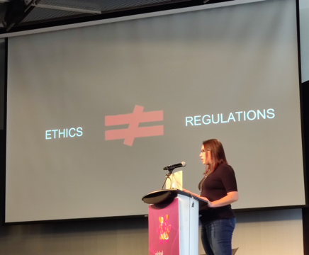A person is giving a presentation. A projected slide says 'Ethics does not equal regulations'.